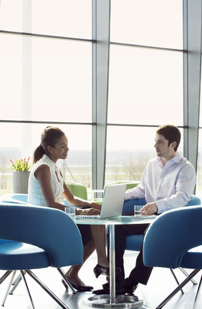 informal clothes: Two business colleagues sitting at a table, having a meeting
