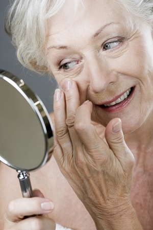 A senior woman looking at her face in the mirror Stock Photo