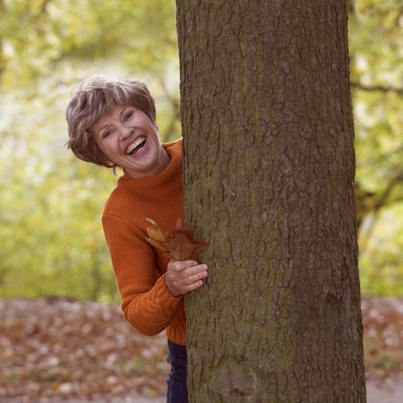 A senior woman standing next to a tree smiling