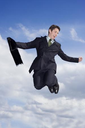 caida libre: Un hombre de negocios que sostiene una cartera, saltando en el aire
