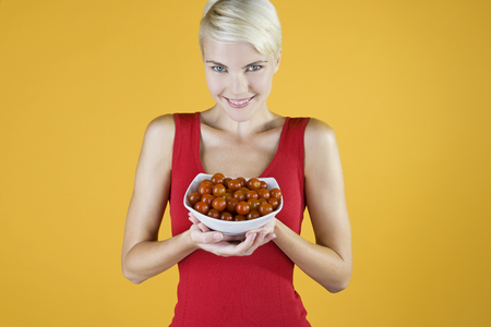 A Young Woman Holding A Bowl Of Cherry Tomatoes