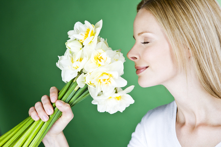 A young blonde woman smelling a bunch of daffodils, side view Stock Photo