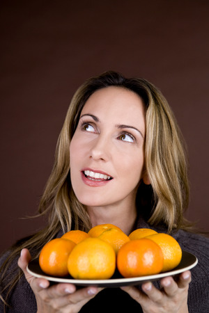 clementines: A mid adult woman holding a plate of clementines, looking up LANG_EVOIMAGES