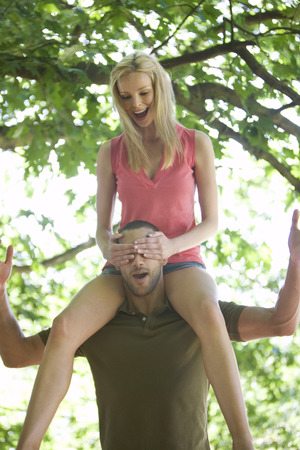 A young man carrying his girlfriend on shoulders in the woods