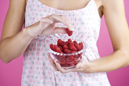 raspberry dress: A Young Woman Holding A Bowl Of Raspberries