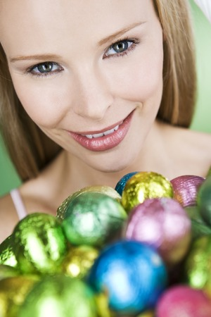 middle easter: A young blonde woman holding a basket of Easter eggs, close-up LANG_EVOIMAGES