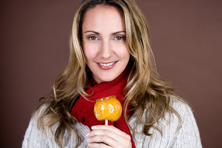 A mid adult woman holding a toffee apple, smiling Stock Photo