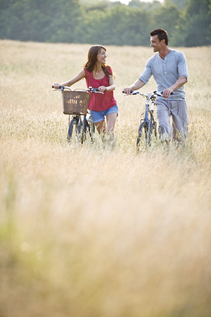 A young couple pushing bicycles through long grass