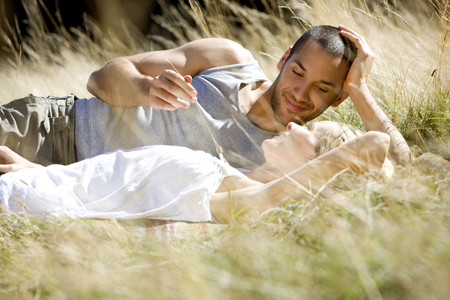 A young romantic couple relaxing on the grass