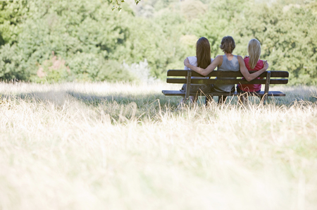 Three young people sitting on a bench in a park Stock Photo
