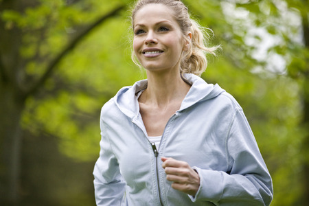 above 30: A mid adult woman jogging in the park LANG_EVOIMAGES