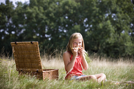 lunchtime: A young girl sitting on the grass, eating melon