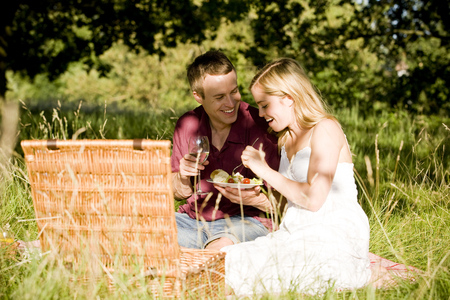 above 30: A young couple sitting on the grass, having a picnic