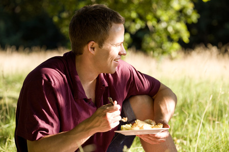 above 30: A young man sitting on the grass, eating LANG_EVOIMAGES