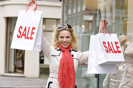 above 30: A mid adult woman holding up some sale bags, smiling
