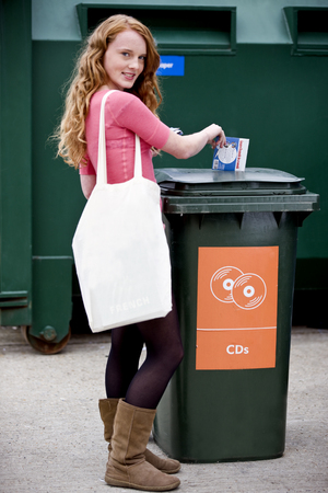 A teenage girl recycling cds