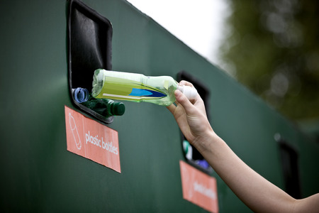 A teenage girl recycling a plastic bottle Imagens