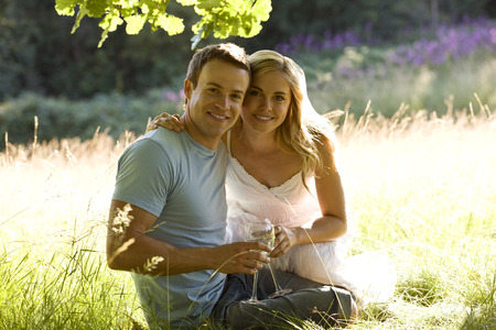 above 30: A young couple sitting on the grass, drinking wine LANG_EVOIMAGES