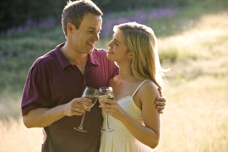 above 30: Portrait of a young couple drinking wine, looking at each other lovingly