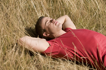 above 30: A young man lying in the sun LANG_EVOIMAGES