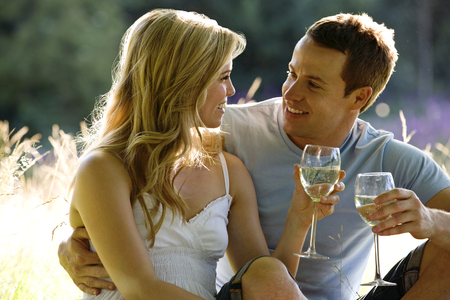 A young couple sitting on the grass, drinking wine Stock Photo