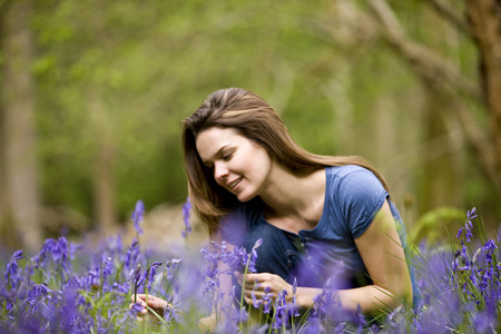 sitting on the ground: A young woman picking bluebells, smiling LANG_EVOIMAGES