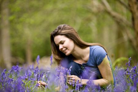 arrodillarse: Joven, mujer, picking, bluebells, sonriente