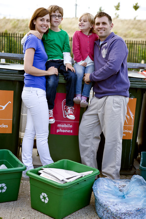 A family standing next to recycling bins