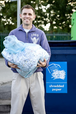 shredded paper: A mid-adult man recycling a bag of shredded paper