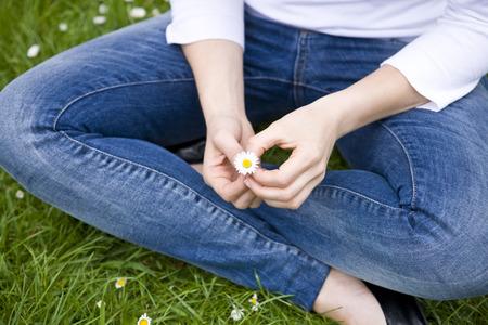 crosslegged: A woman sitting cross-legged, holding a daisy LANG_EVOIMAGES