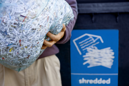 shredded paper: A man recycling a bag of shredded paper