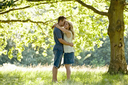 above 30: A young couple standing beneath a tree, embracing LANG_EVOIMAGES