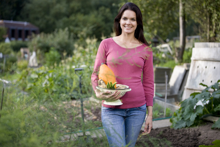 self sufficient: A young woman holding a colander full of vegetables