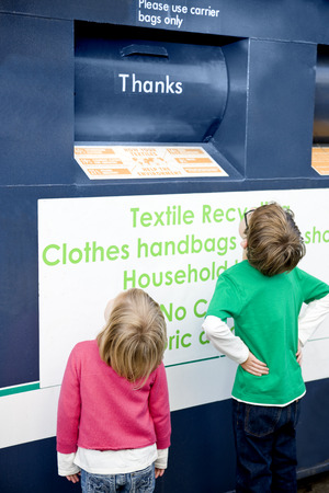 niños reciclando: Dos niños jóvenes que buscan en un contenedor de reciclaje de textiles