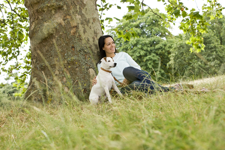 stroking: A young woman sitting on the grass, stroking her dog LANG_EVOIMAGES