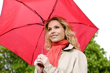 above 30: A mid adult woman holding a red umbrella