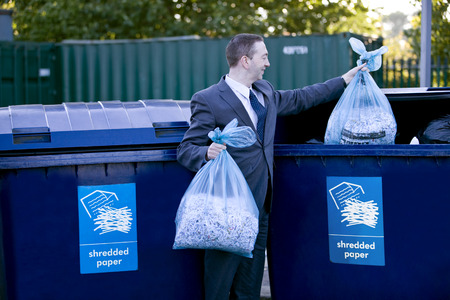 A businessman recycling bags of shredded paper LANG_EVOIMAGES