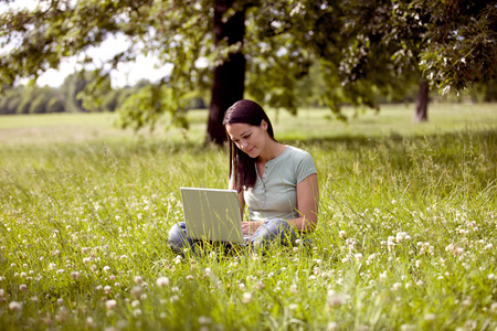 crosslegged: A young woman sitting on the grass using a laptop