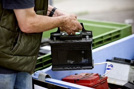 A senior man recycling a car battery Imagens - 64792949
