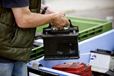 Een senior man recycling van een auto-accu