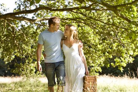 persona caminando: Una joven pareja que lleva una cesta de picnic LANG_EVOIMAGES