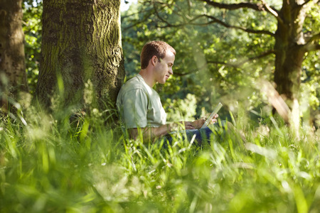 above 30: A young man leaning against a tree, using a laptop