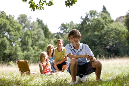 A family having a picnic, young boy sitting on a football Stock Photo