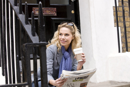 above 30: A mid adult woman sitting on steps, holding a coffee and a newspaper