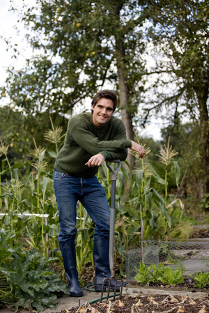 self sufficient: A young man leaning on a fork on an allotment