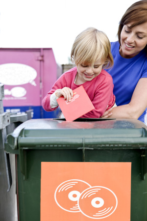 A mother and daughter recycling a cd