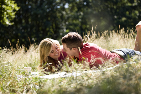 A young couple lying in the grass, relaxing