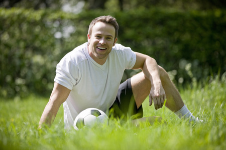 above 30: A young man sitting on the grass with a football LANG_EVOIMAGES