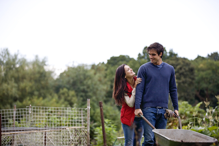 carretilla: A young couple pushing a wheelbarrow on an allotment