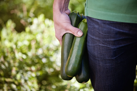 courgettes: A man holding courgettes